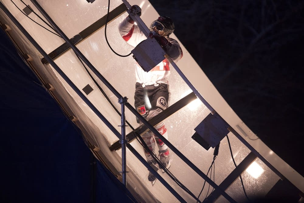 A racer uses the railing to climb the wall.