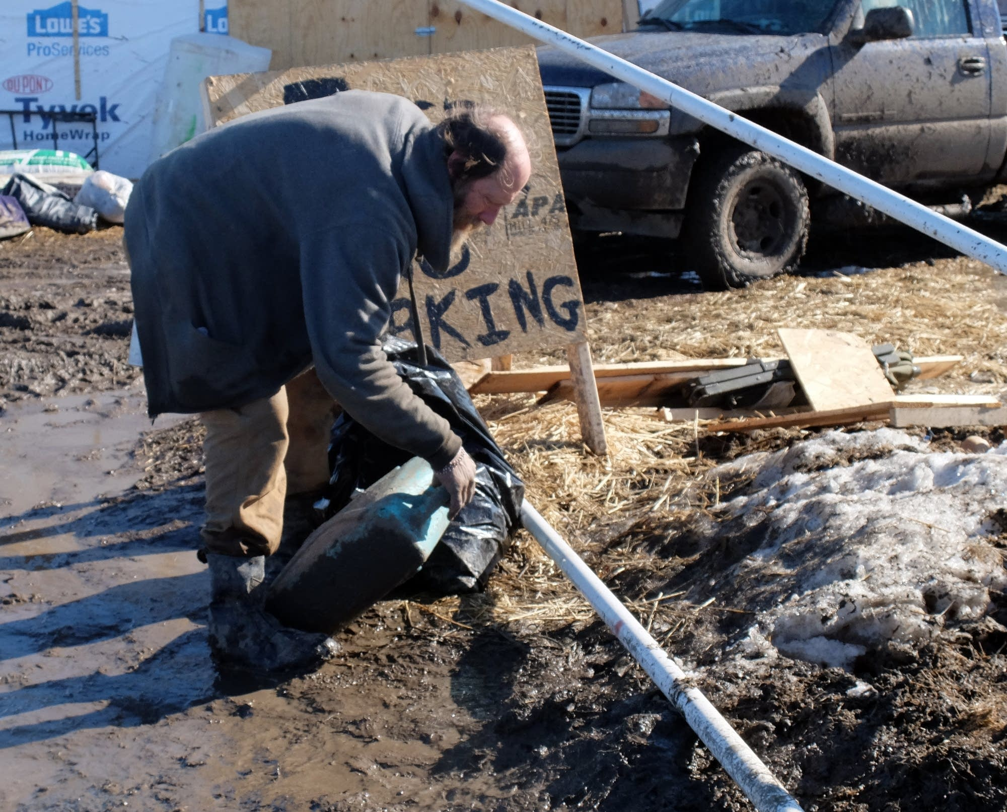 Eric Wallace-Senft picks up debris at Oceti Sakowin camp.