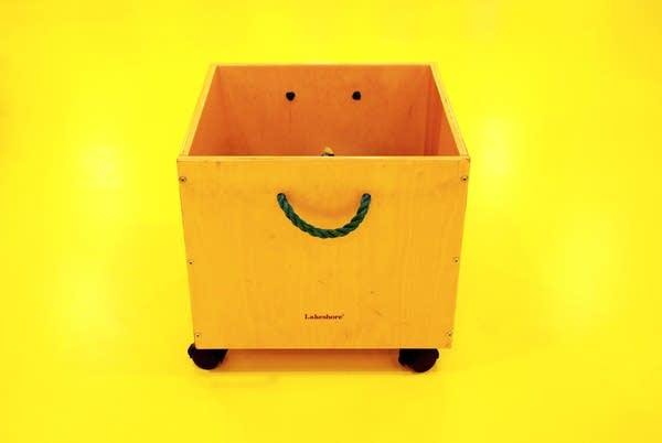 Wooden toy box on wheels with rope handle that looks like smiley face