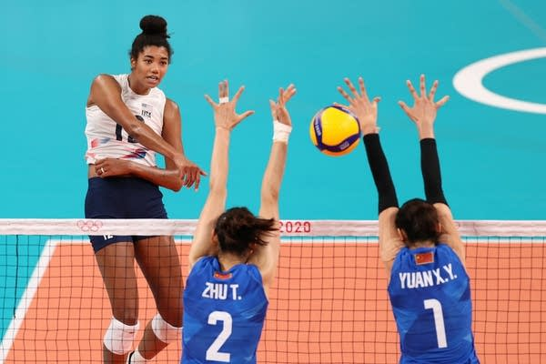 A volleyball player reaches for a strike
