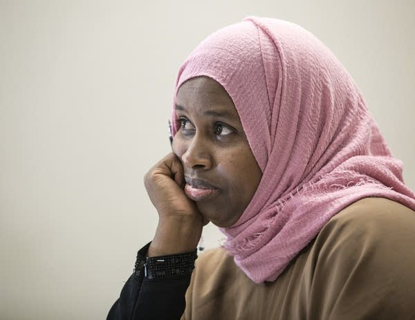 A woman wearing a pink hijab listens