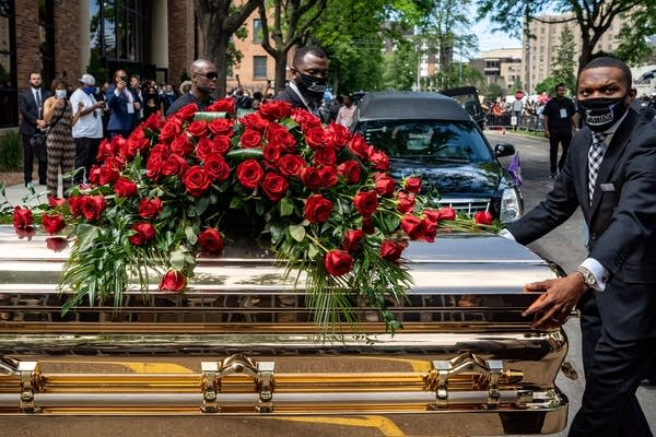 A casket with roses on top of it.