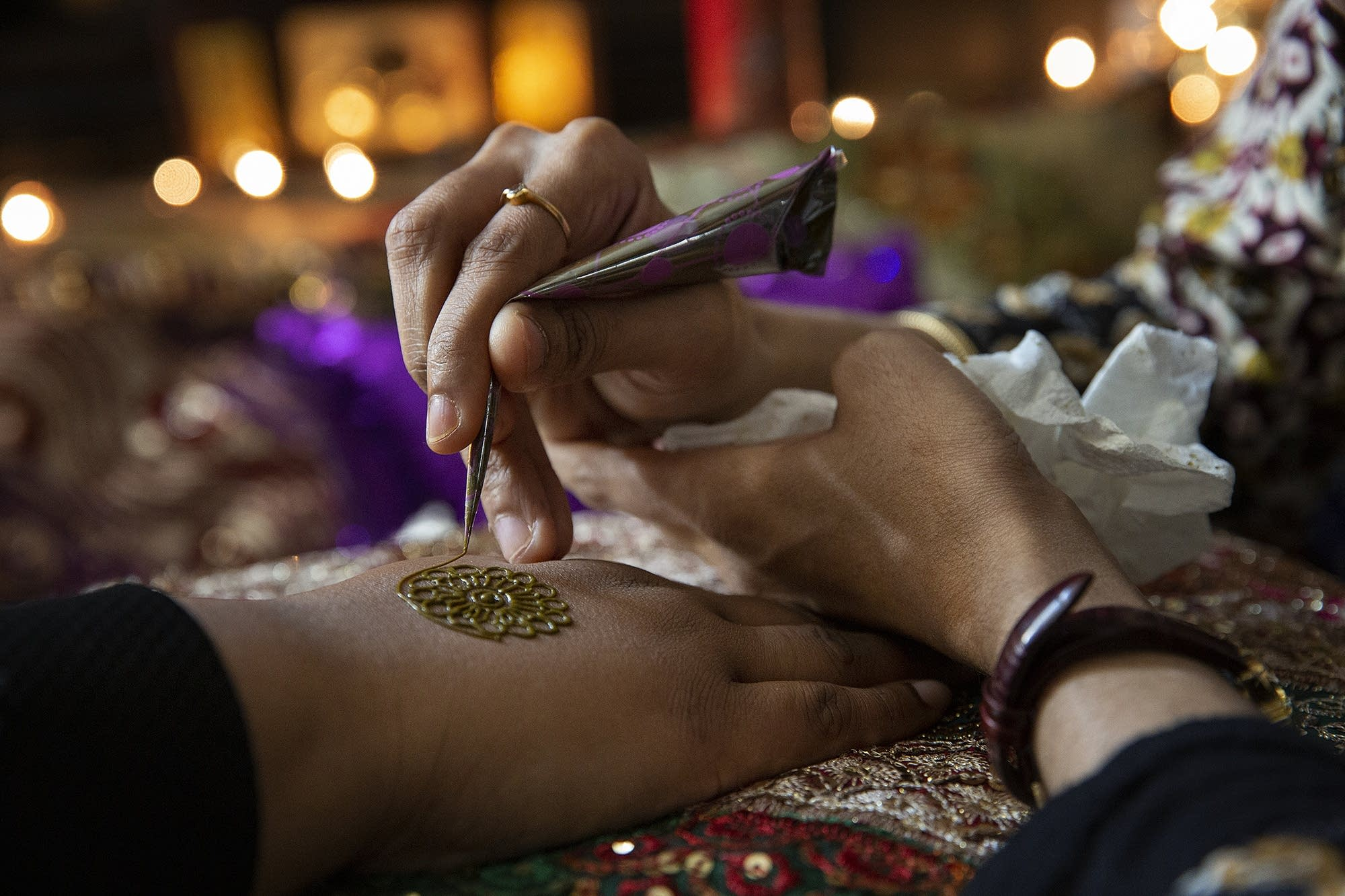 Hajira Begum draws a mandala henna design on Fatma Sheekh's hand.
