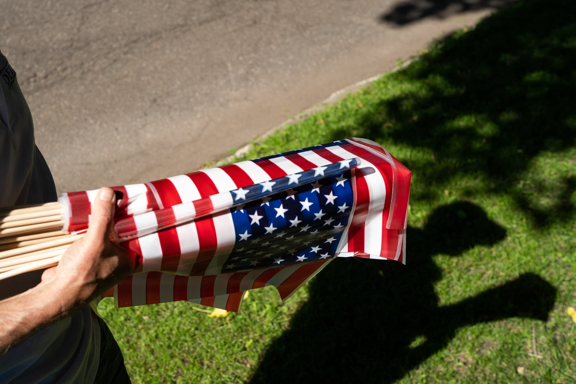 Tom Edelstein holds a bundle of American Flags.