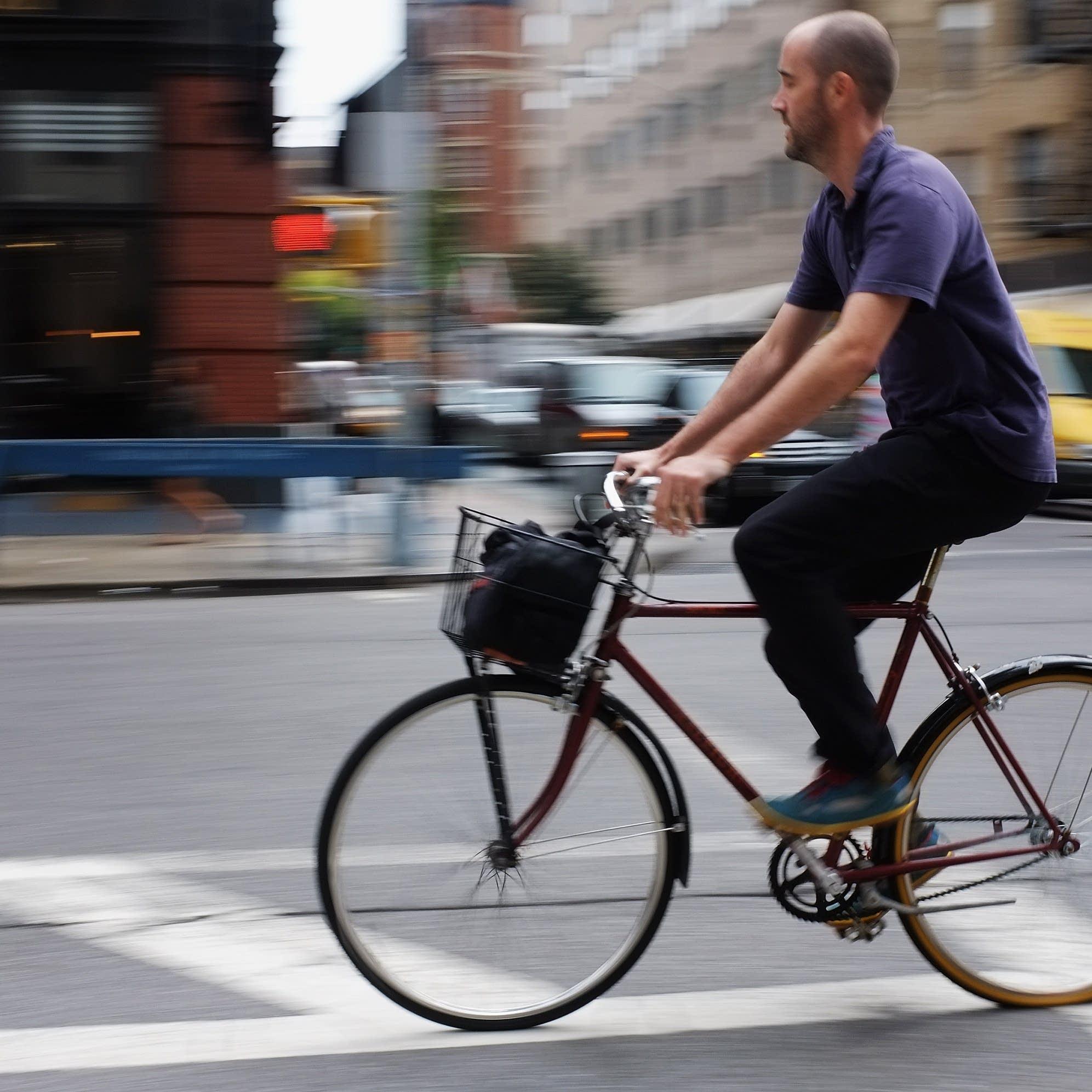 A man rides a bicycle along a Manhattan street.