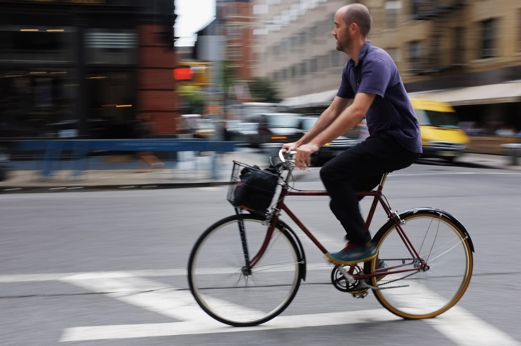 A man rides a bicycle along a Manhattan street.
