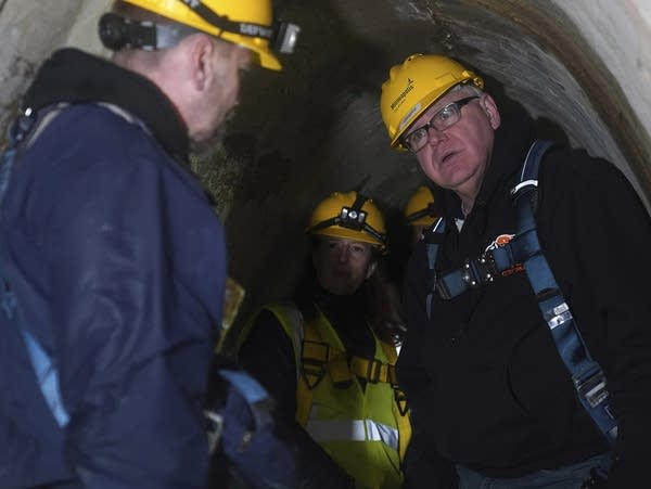 Gov. Tim Walz tours a storm tunnel with public works officials.