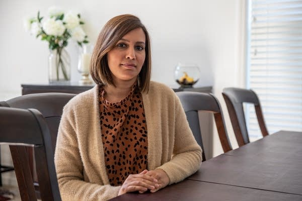 A woman in a tan sweater sits at a table inside.