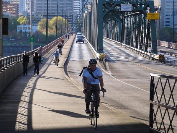 Cyclists and pedestrians share a sidewalk on a Portland bridge
