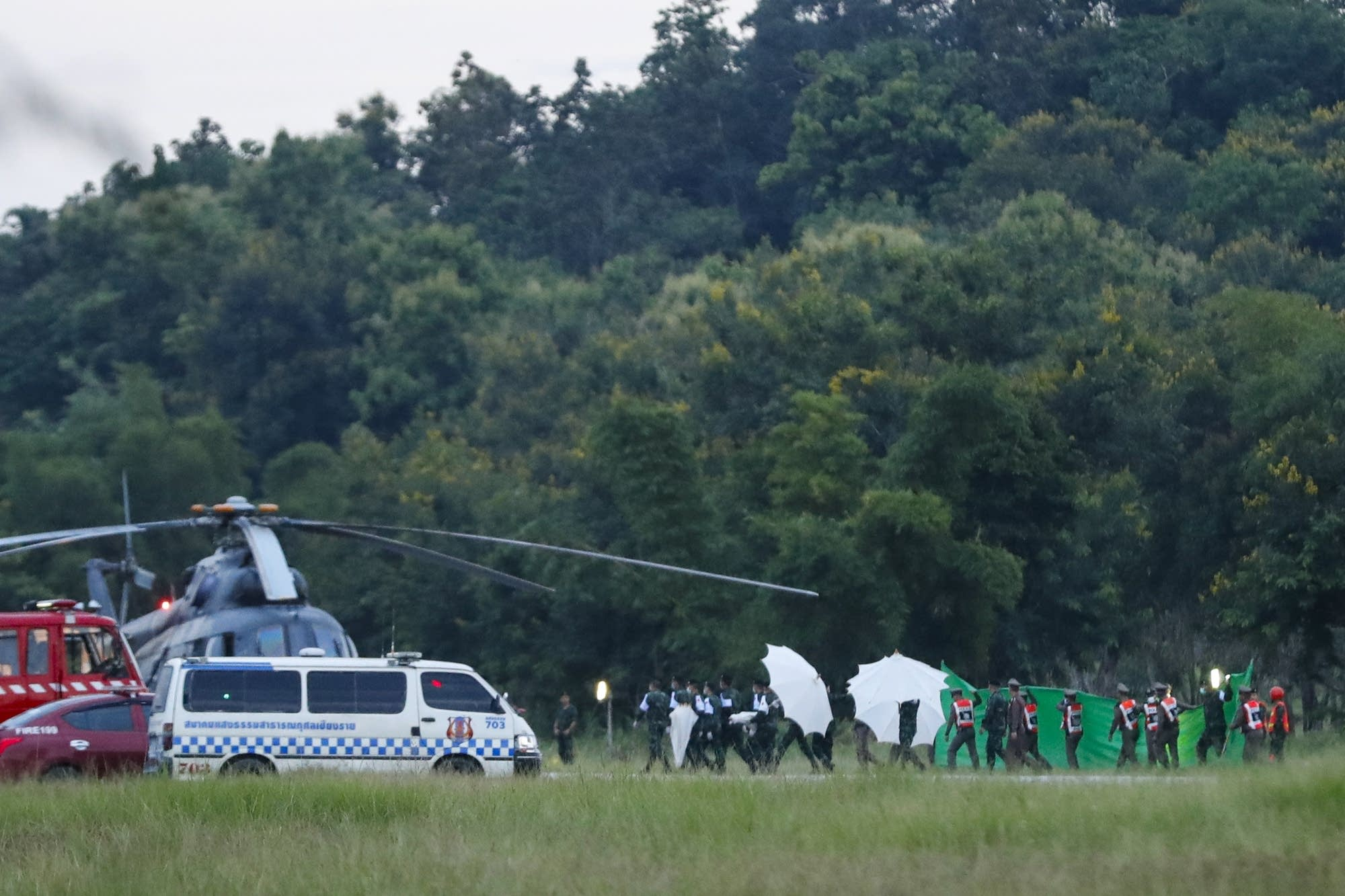 An emergency team rushes to a helicopter believed to be carrying a boy.
