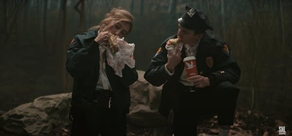 TV Image of two cops eating hoagies at crime scene in the woods