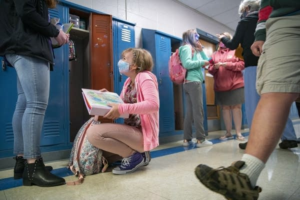 A girl in a face mask kneels in front of a locker as others walk by