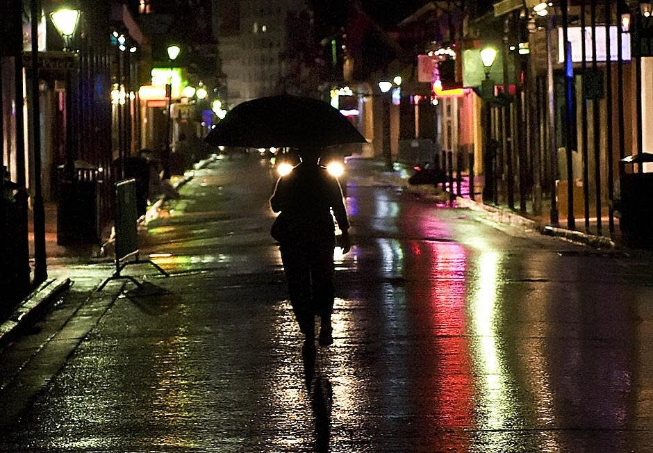 A woman walks down Bourbon street in the rain