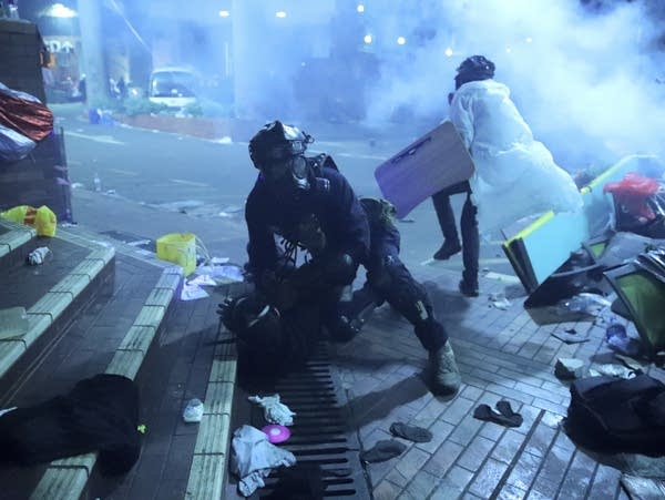 A police officer in riot gear detains a protester