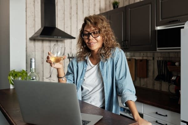 A woman drinking wine while using her laptop