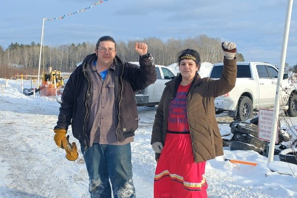 A man and a woman raise their fists.