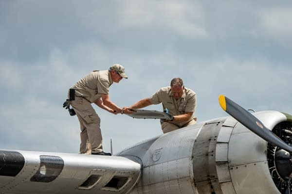 Matt Ohr, left, and Hank Morrissey, right, remove a panel from a B-17G