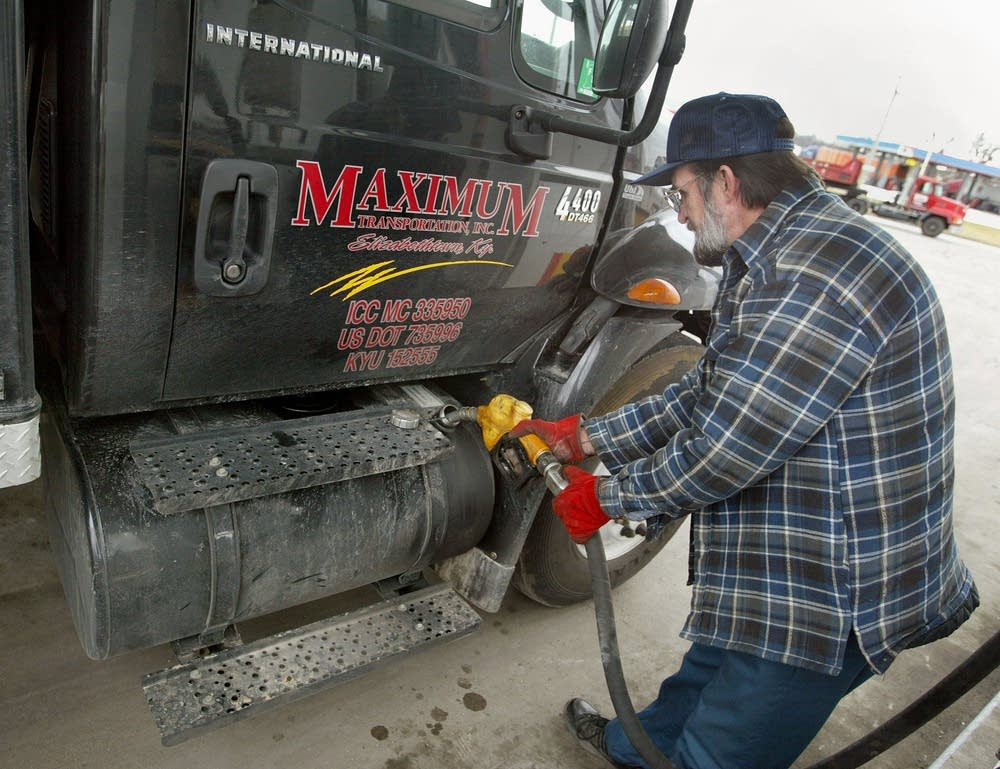 Trucker James Baker pumps fuel into his rig