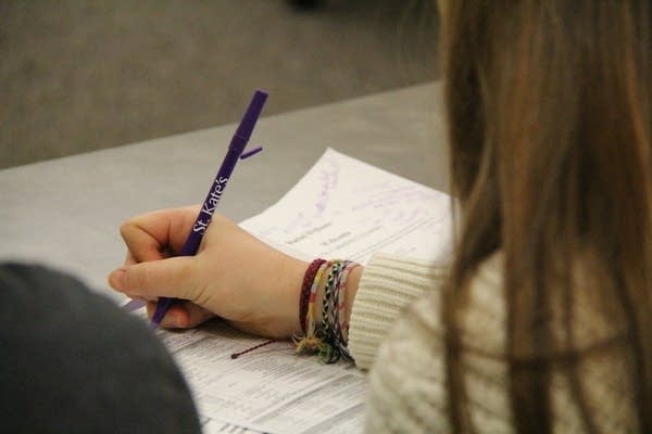 A student takes notes during an information session.