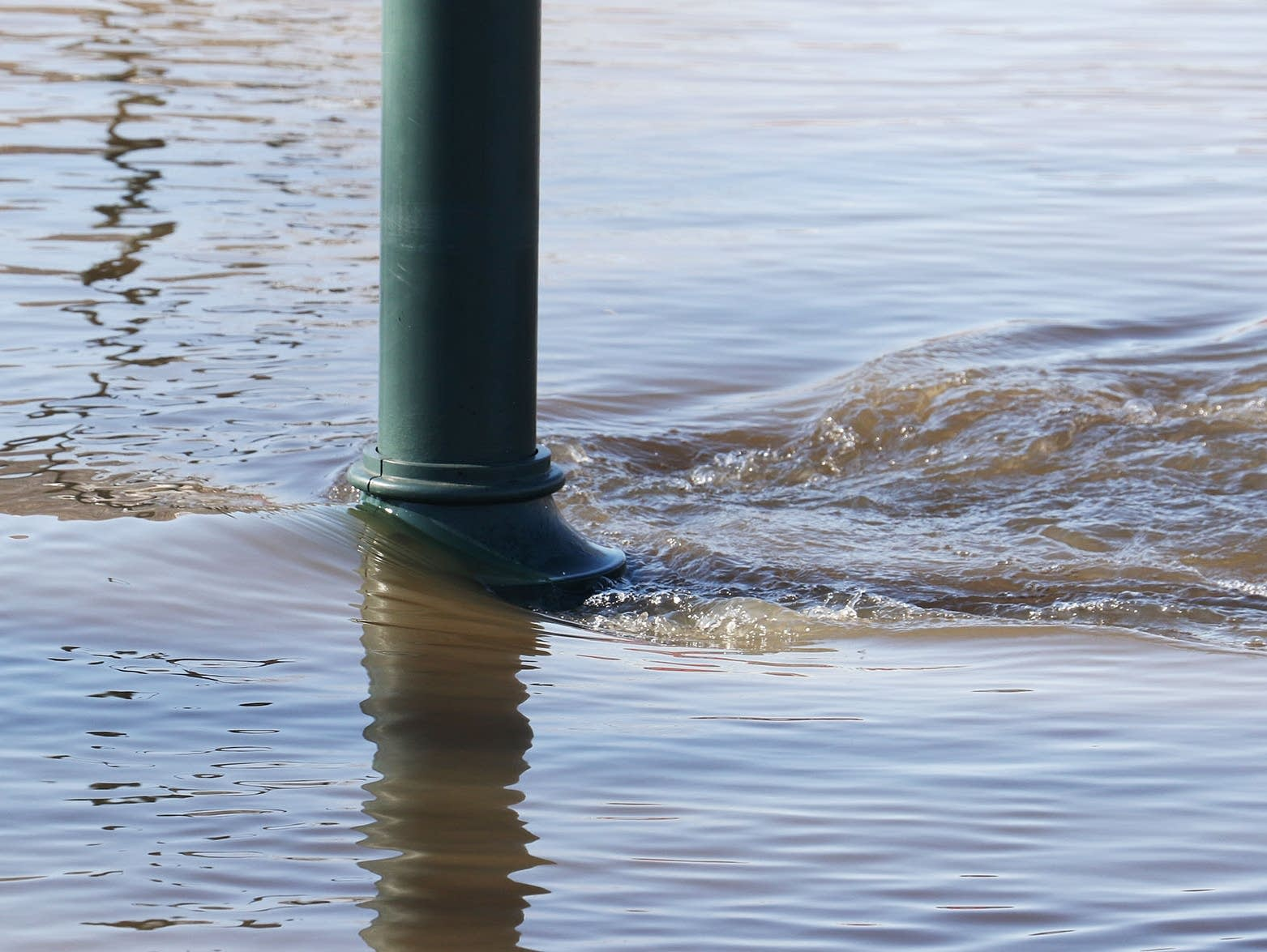 The current of the Mississippi River is visible at a flooded lamppost
