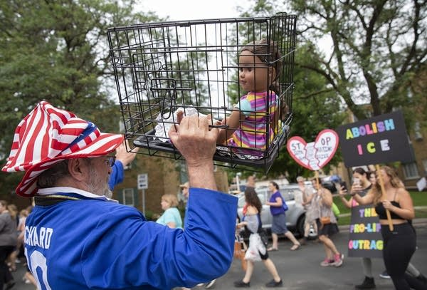 Clarence Richard of Minnetonka, Minn. holds a doll in a cage.