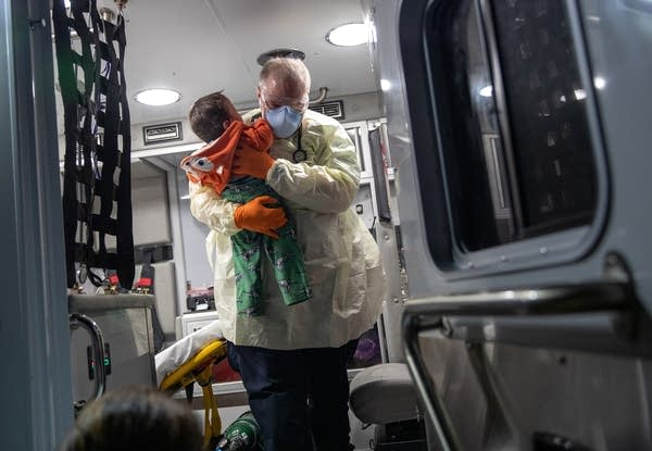 A paramedic carries a baby out of ambulance.