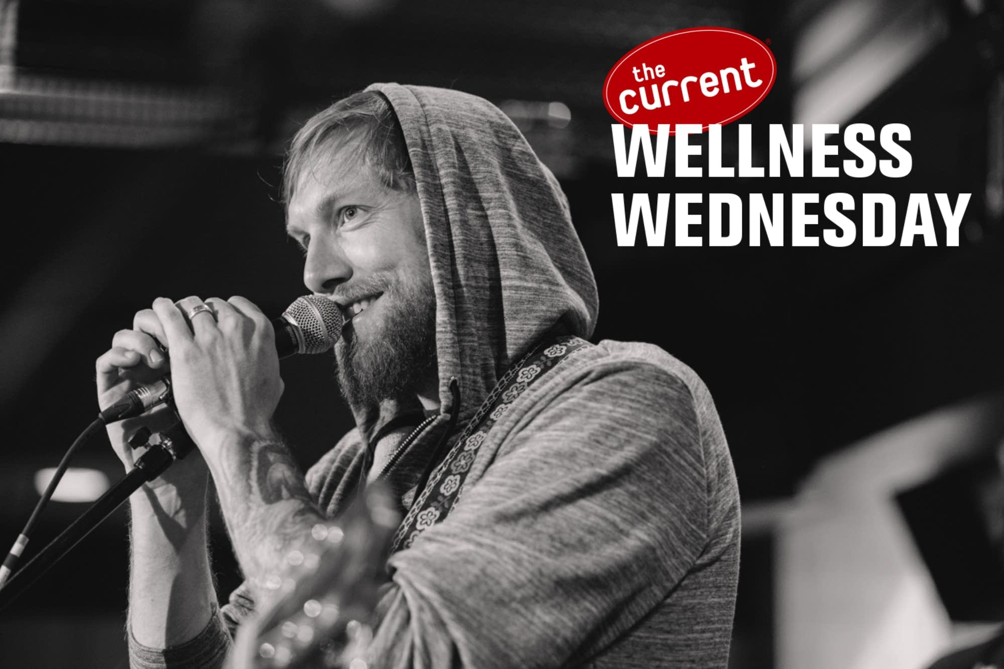 Man speaking into microphone with Wellness Wednesday logo.
