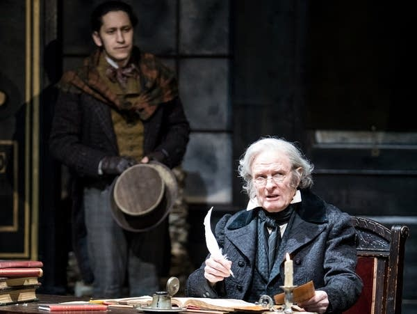 A man holds a quill pen at a desk for a play.
