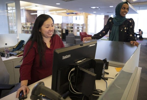 A woman works in front of a computer while talking with another woman.