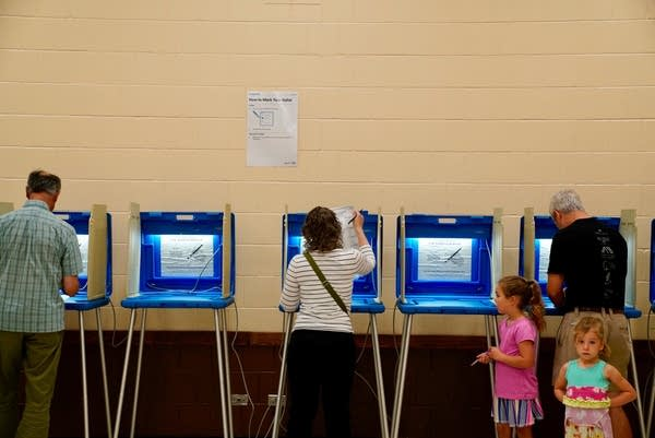 Justin Coyne, right, votes at the Pershing Park Recreation Center.