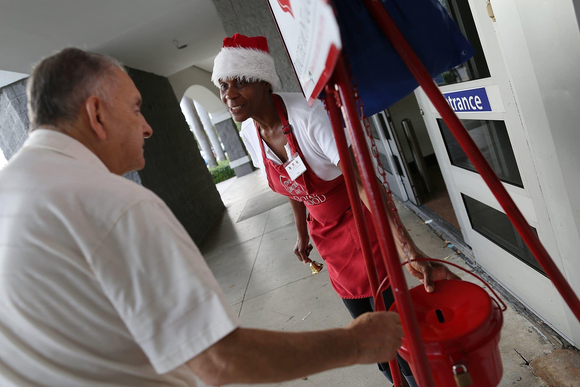 Kim Simmons looks on as Alvaro Burgos makes a donation.