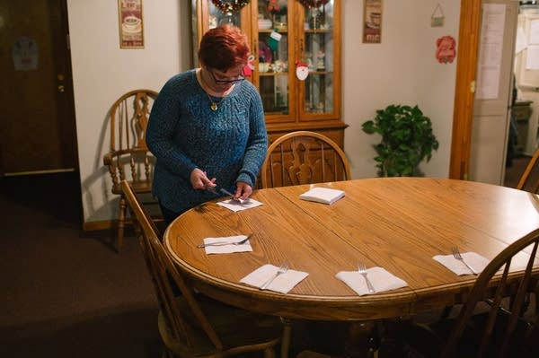 Pauline helps set the table for dinner at her group home.