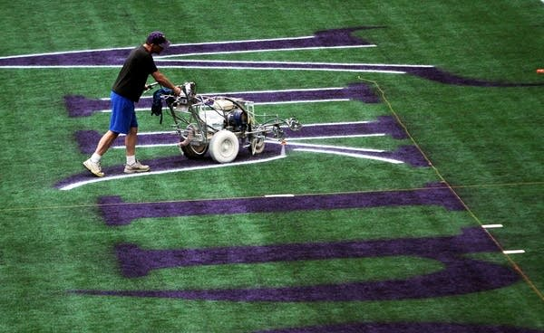Wayne Enger paints the end zone for the final season of Vikings football at Mall of America Field in Minneapolis, Minn. Tuesday, Aug. 6, 2013.