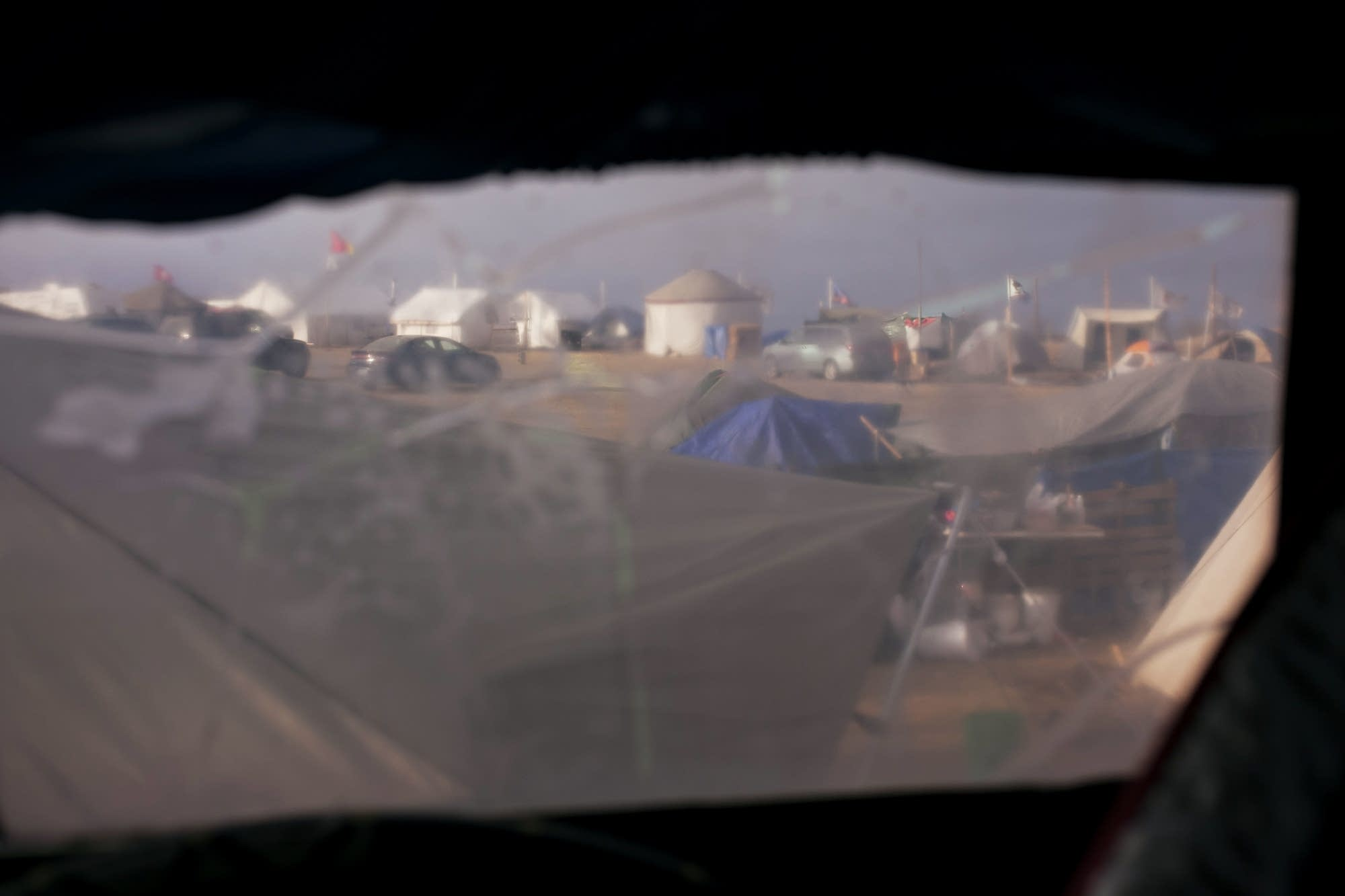 Part of the camp is visible through Kasto's window.