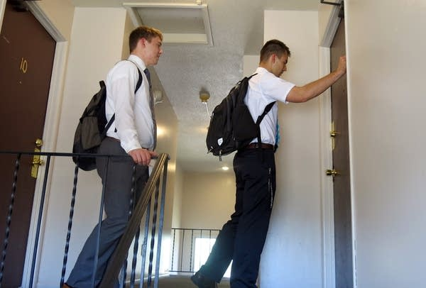 Tanner Smedley, with Joseph Smith, knocks on an apartment door.