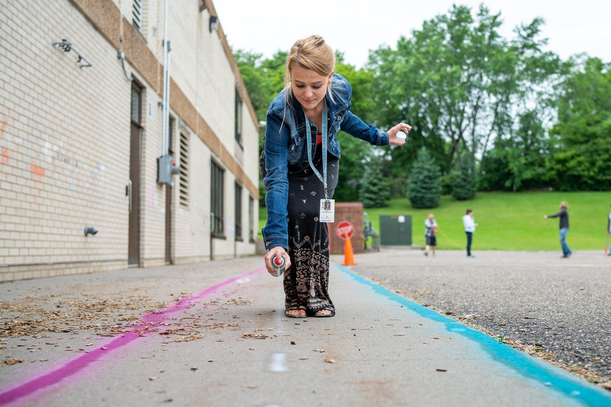 Teacher Ashley Martinson uses spray chalk to make a course.