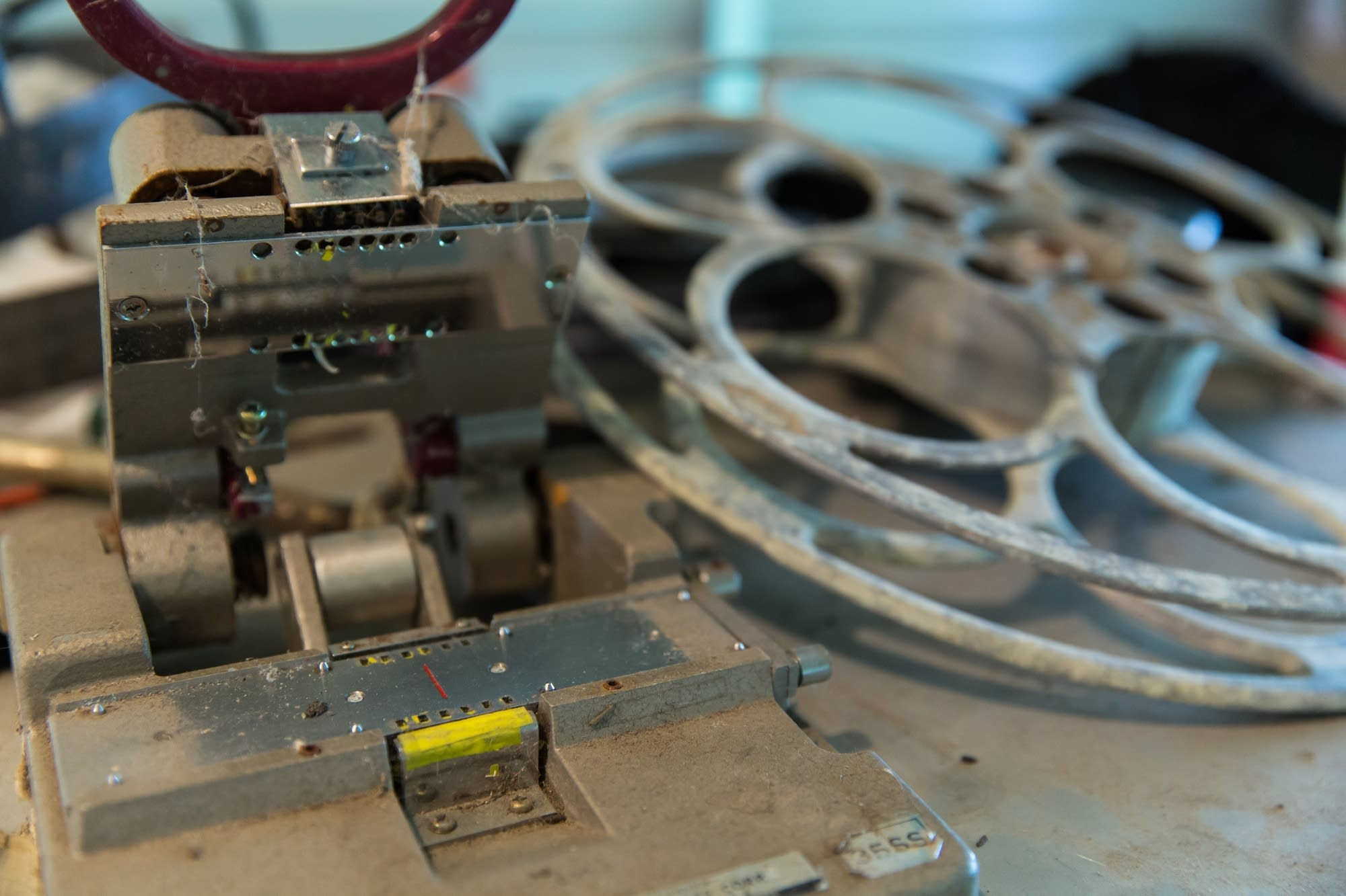 An old film cutting machine sits alongside an empty film reel.