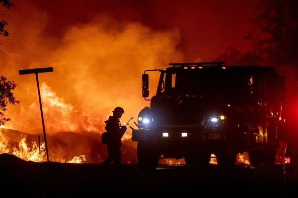 A firefighter lights backfires during the Carr fire in Redding