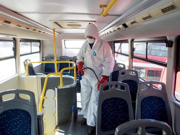 A worker disinfects a public bus