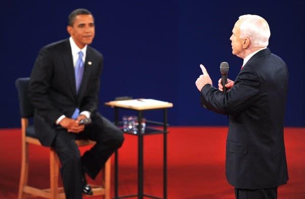 Sen. Barack Obama (L) listens to Sen. John McCain