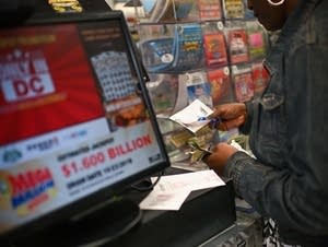 A woman buys Mega Millions tickets.