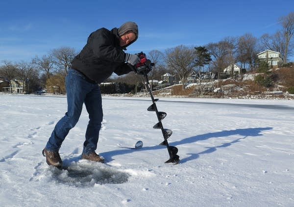 Dan Jasper clears a hole he cut in Lake Minnetonka