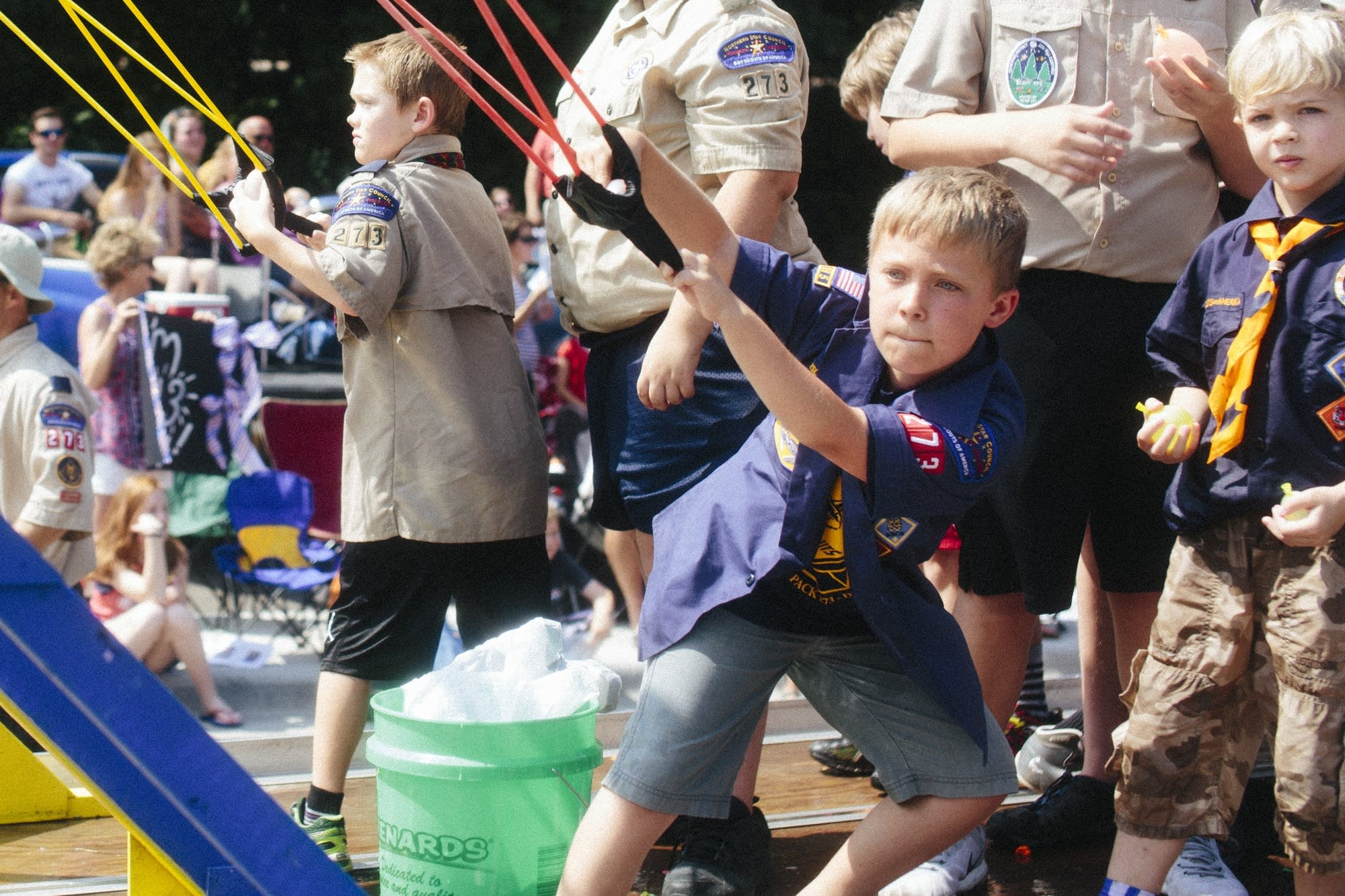 A Cub Scout from Pack 273 aims a water balloon.