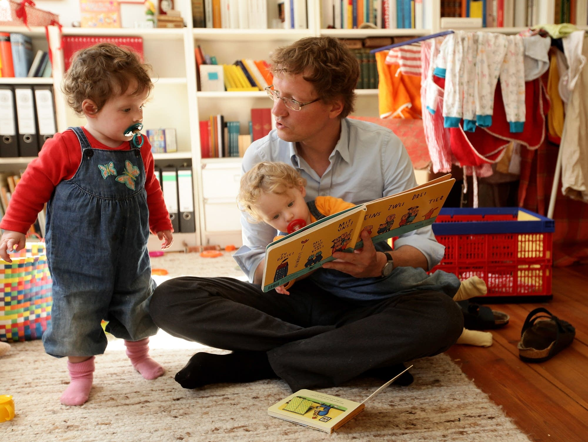 A father reads to twin daughters