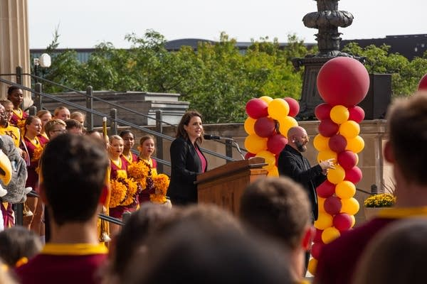 A woman speaks at a podium in front of maroon and gold balloons.