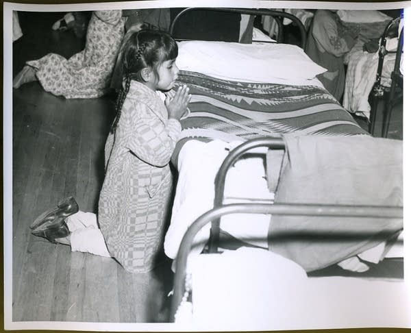 A young girl prays at her bedside