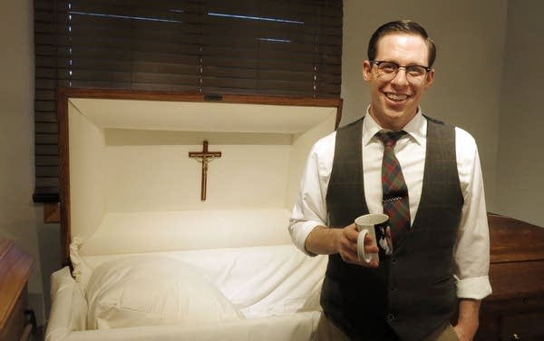 A man stands in front of a casket.