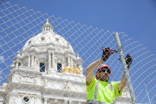 worker cuts zip ties holding Capitol fence together