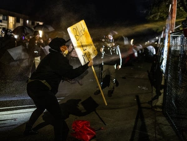 A demonstrator holds up a sign as they are pepper-sprayed