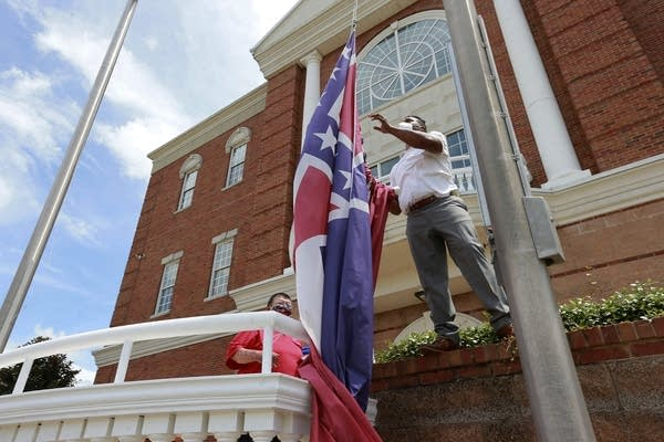 A man takes down a flag in front of a city hall.